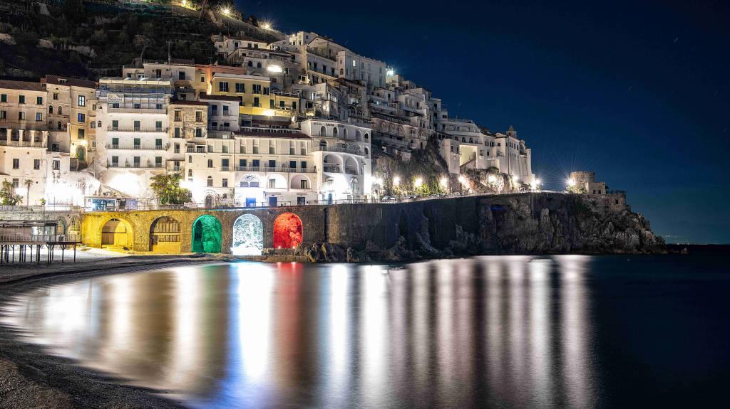 Amalfi. Il Comune illumina col tricolore le arcate della Marina Grande. La speranza da uno dei paesaggi simbolo d