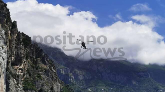 Positano, le operazioni di aggancio della rete con l'elicottero: auto bloccate in lunghe code